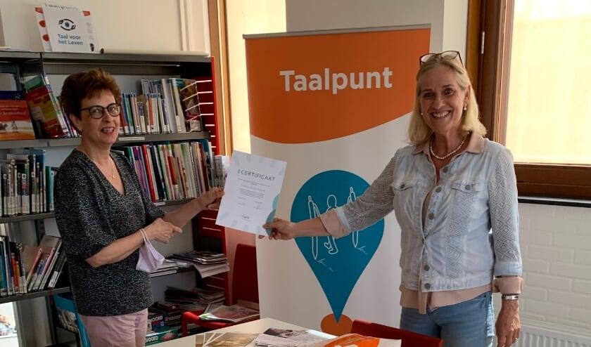 <p>Bibliotheekdirecteur Hetty van de Weg en Taalpuntdocent Barrie Nitrauw tonen trots het behaalde certificaat.</p>