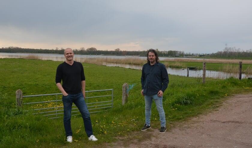 <p>Dick van de Streek (links) en Jan van Ommen wijzen de locatie aan waar havenkom, steigers en doorstroomgeul worden aangelegd (foto Dick van der Veen)&nbsp;</p>