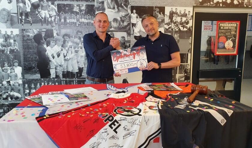 <p>Mede-organisator Coen Scheurwater (links) toont samen met Jan-Willem Zwang de opbrengst van de veiling.</p>