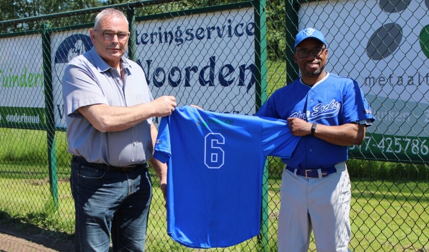 <p>Teus van Dooren (links) reikt het eerste nieuwe clubshirt uit aan trainer Osrick Anita.</p>