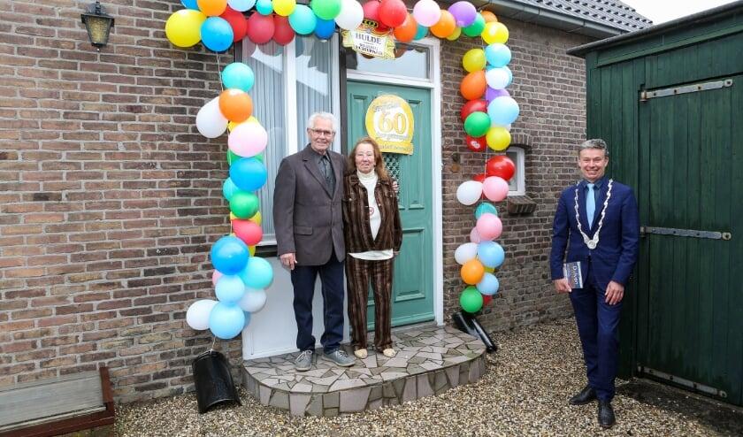 <p>Henk en Nel Meijer in de feestelijk versierde deuropening van hun huis. Rechts burgemeester Huub Hieltjes van Duiven die het diamanten paar namens de gemeente kwam feliciteren.</p>