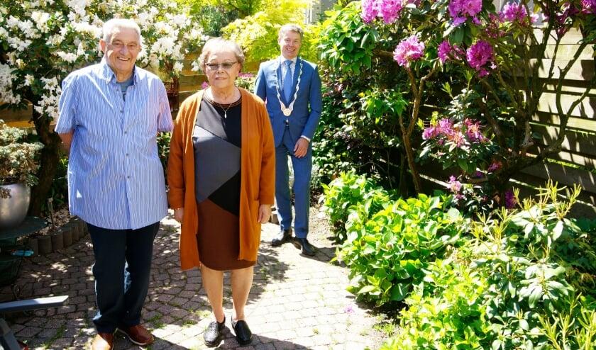 <p>Rinus Hartemink en Pieteke Hartemink-Grinwis poseren samen met burgemeester Huub Hieltjes.</p>