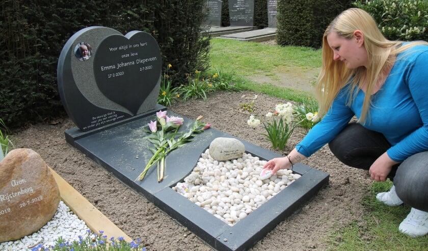 Eline legt een steentje op het grafje van Emma, het jonggestorven dochtertje van de schrijver van dit artikel. (foto: Marco Diepeveen)