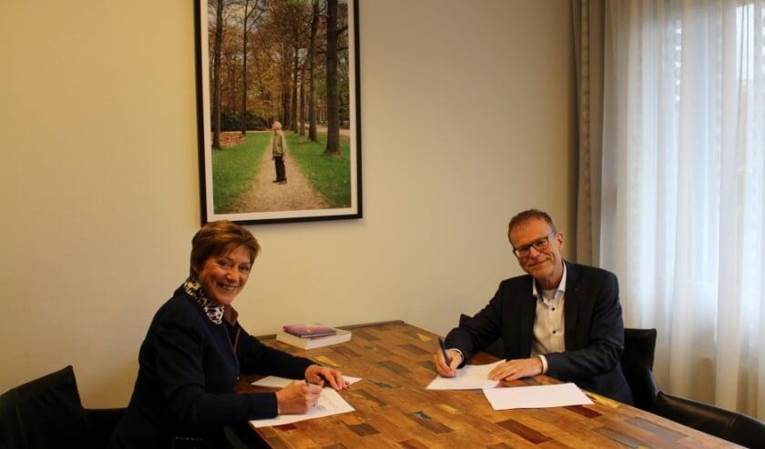 De voorzitter van de cliëntenraad, Lyda Sneevliet, en de bestuurder van Zorgverlening Het Baken, Wilfred Juurlink, ondertekenen de samenwerkingsovereenkomst