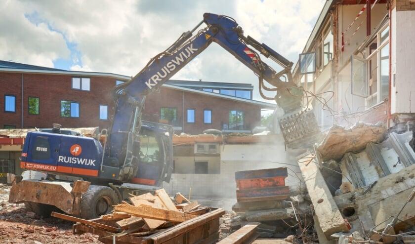 <p>Met grote machines wordt voorzichtig gemanoeuvreerd bij de sloop van de oude Bunterhoek.</p>