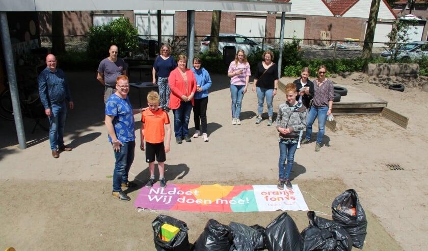 Vrijwilligers poseren op gepaste afstand van elkaar met de 'buit' van de zwerfvuilactie in de Bestse wijk De Leeuwerik.