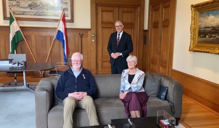 <p>Gedecoreerde Hoogvlieter Aad Dolder zit er enigszins beduusd bij terwijl zijn vrouw Gerrie er trots naast zit en burgemeester Aboutaleb er breed lachend achter staat.</p>