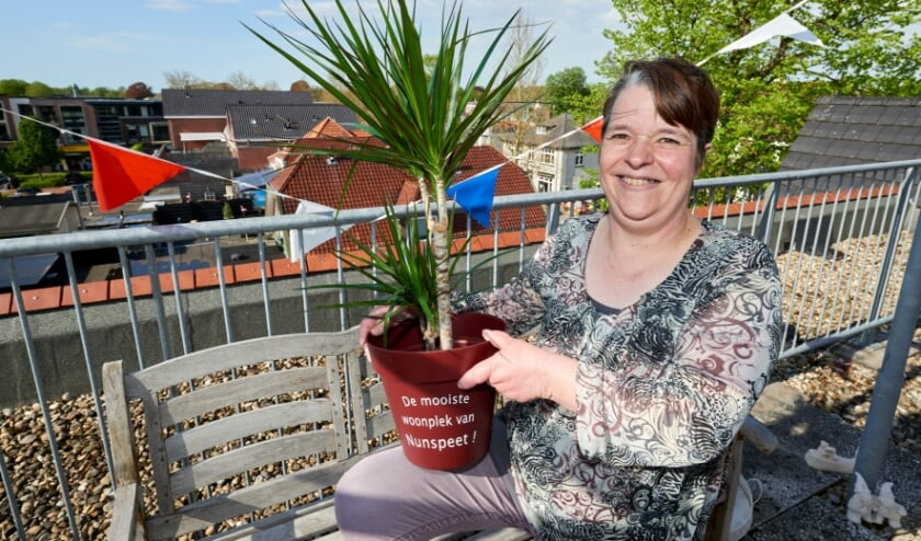 <p>Joke Brandsen op het dakterras met de plant die ze kreeg voor het jubileum.</p>