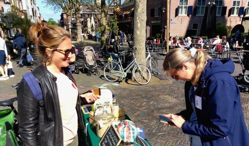 <p>Wanda Hoogendoorn koopt bij de Zero Waste kraam. Rechts Ilja Gort.</p>
