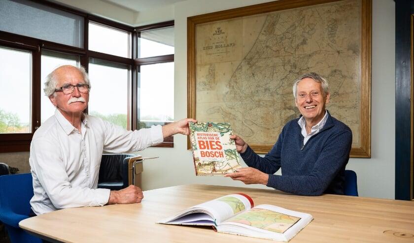 <p>Auteur Wim van Wijk (l) overhandigt het eerste exemplaar van de Biesboschatlas aan dijkgraaf Jan Bonjer.</p>