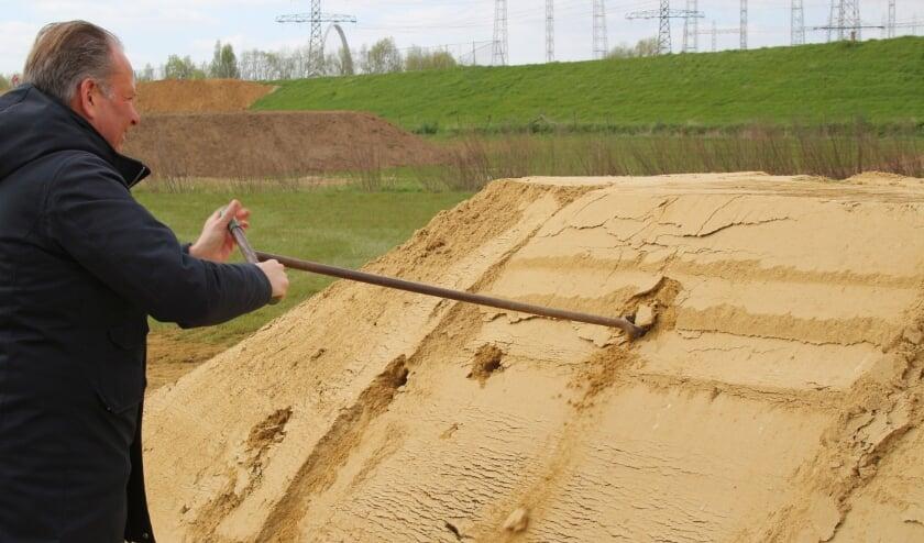 <p>Wethouder Noël Vergunst boort een gat in een zandwand zodat oeverzwaluwen er kunnen nestelen.</p>