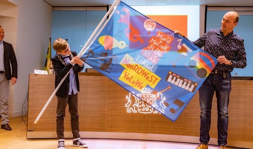 <p>Kinderburgemeester van Harderwijk Daan Boersma met de winnende vlag van de Gabrielschool Putten. (foto: Ton Pors)</p>