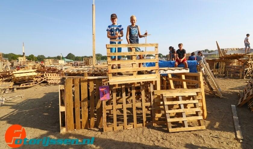 <p>Trotse kinderen op hun zelfgebouwde hut tijdens Houtdorp..</p>