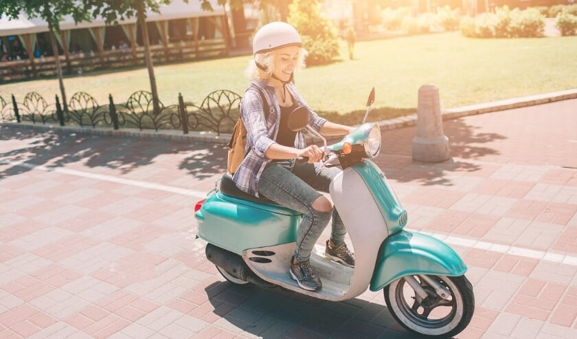Young cheerful girl driving scooter in in city. Portrait of a young and stylish woman with a moped.