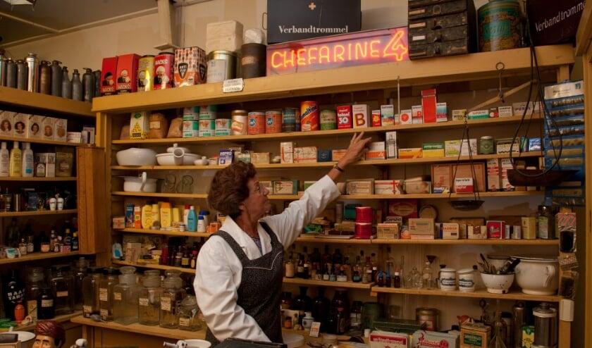 <p>Erfgoedvrijwilliger in de drogisterij van het Oude Ambachten & Speelgoed Museum in Terschuur, Gelderland</p>