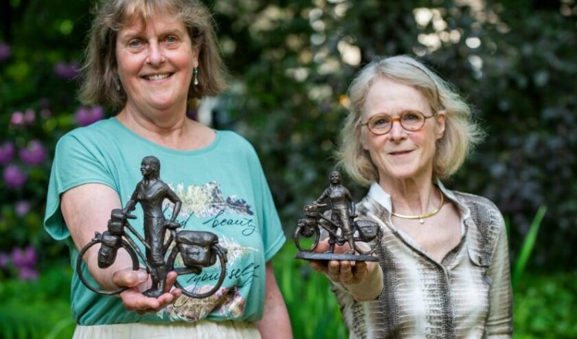 <p>Dianne Hamer (links) en Janneke Goldberg van de Epe voor Epe-organisatie tonen replica&#39;s van De Fietsster gemaakt door beeldhouwster Greet Grottendieck. Deze worden verloot tijdens de editie van 2022.</p>