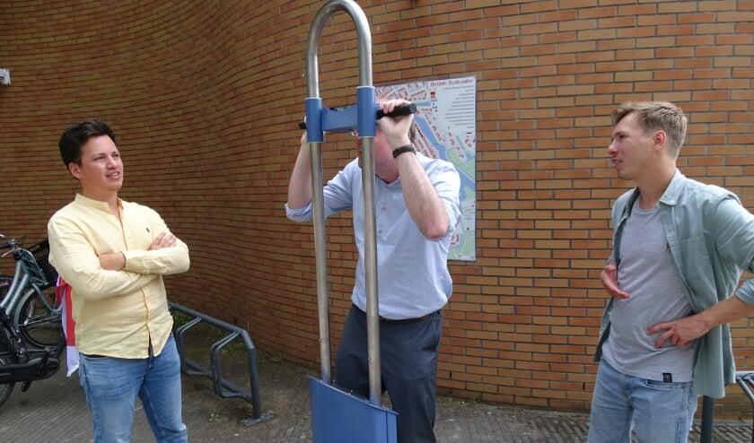 Bas Lont kijkt door de VR paal de geschiedenis in, de makers Jurjan Rietveld (re) en Rick Voll (li)