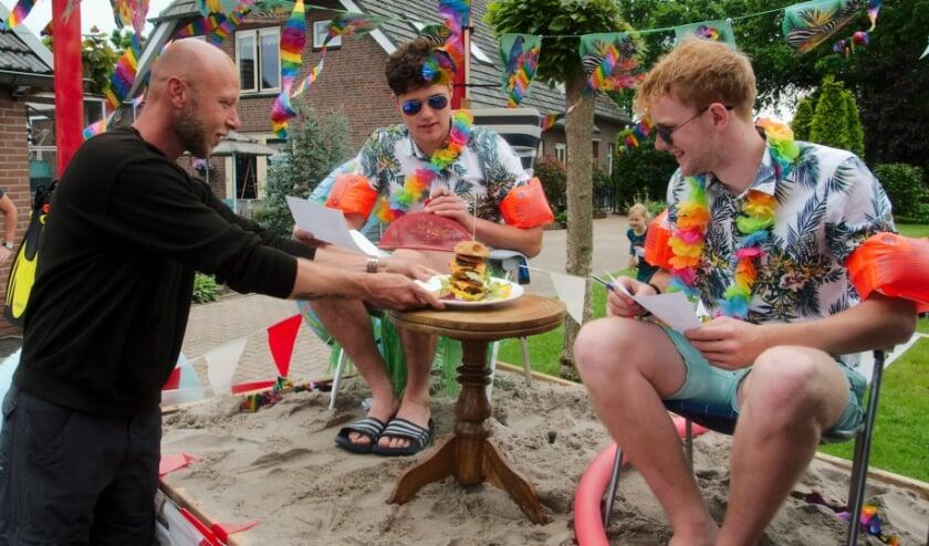 <p>Barbecueman Clenn vd Berg serveert jury Daan Hobert en Wout Kemper een overheerlijke hamburger.&nbsp;</p>